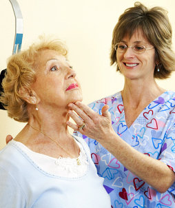 Physical therapist in chiropractors office helping a senior woman exercise her neck