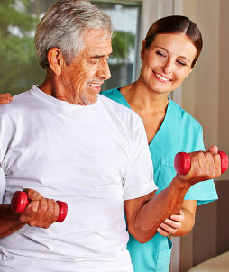 Senior men with dumbbells in rehab with a physiotherapist