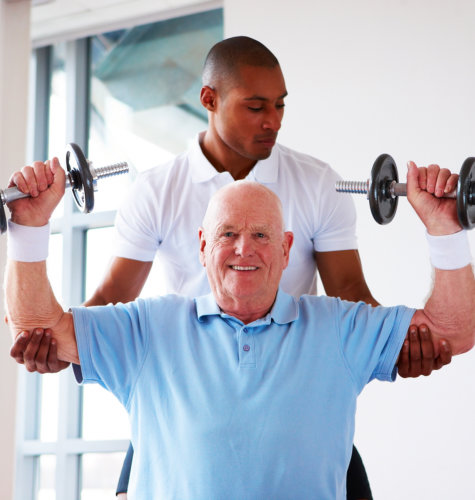 physical therapist assisting elderly patient in lifting weights